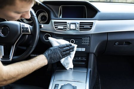 Man polishes a car interior with a cloth