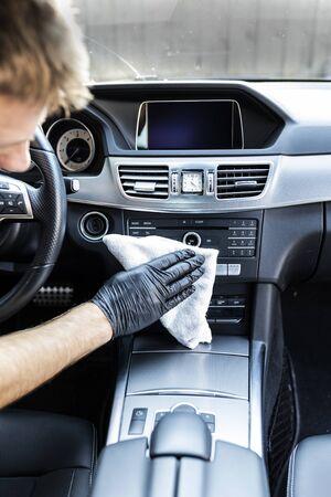 Man polishes a car interior with a cloth Фото со стока
