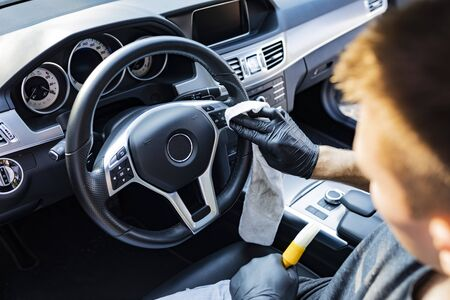 The man cleans the steering wheel with specialized care products