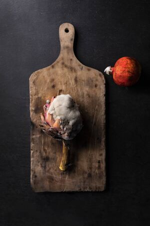 A moldy artichoke and pomegranate placed on a wooden chopping board, on a dark background, top view. A Composition of rotten vegetables. Stockfoto