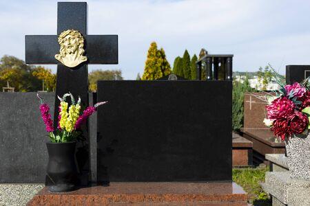 Pierre tombale avec un espace pour une inscription. Une pierre tombale en granit bien entretenue et élégante au cimetière. Toussaint. Visiter les tombes des êtres chers.