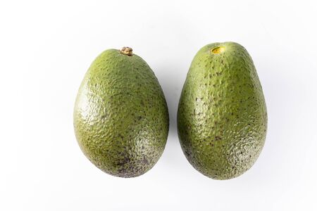 Whole avocado fruits. A ripe green avocado fruits on a white background, top view, close-up.