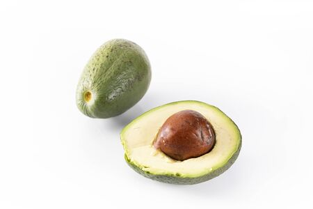 Whole avocado and halved one, with visible stone. A ripe avocado fruits on a white background.