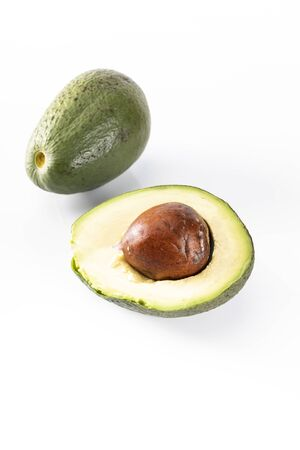 Whole avocado and halved one, with visible stone. A ripe avocado fruits on a white background, close-up.