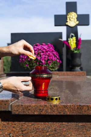 Paying respect to deceased loved ones on All Saints' Day. A man lights a red graveyard candle on a tombstone with a match. A granite gravestone in the cemetery decorated with flowers and a candle.