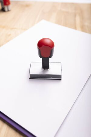 A traditional ink rubber stamp placed on a paper folder. Office accessories on a wooden desk. Stockfoto