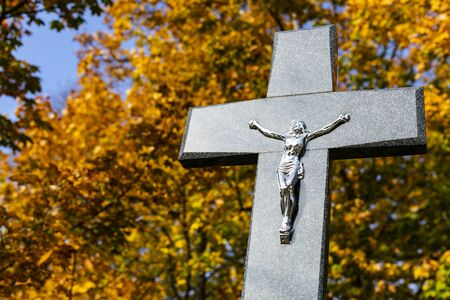 Christian cemetery on a sunny autumn day. All Saints Day. Tombstone with a big Christian cross. Monument on the gravestone. Autumn trees in the background