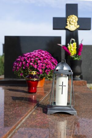 Pink chrysanthemums in a flowerpot and grave lanterns on a granite tombstone, on a cemetery. Glass, grave candles. All Saints Day on a Christian cemetery. Votive candles lit in memory of the dead.