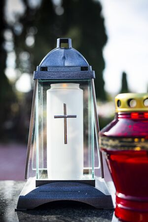 A composition of grave candles on a marble tombstone, on a cemetery. An elegant, glass, grave candle. All Saints Day customs on a Christian cemetery.