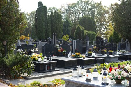 Graves at a Christian cemetery in autumn. All Saints Day. Tombstones decorated with flowers and grave candles. Stock Photo