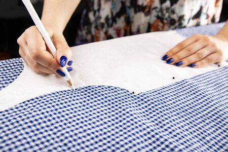 The woman draws a tailor template on the material.