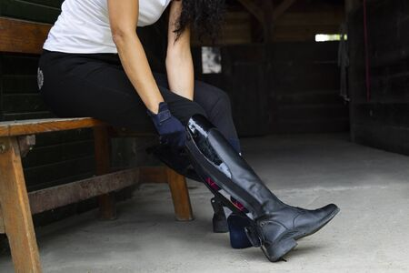 Stud, woman puts on professional leather riding boots.