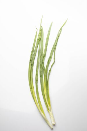 Green chives with onion on a white background. spring vegetables.