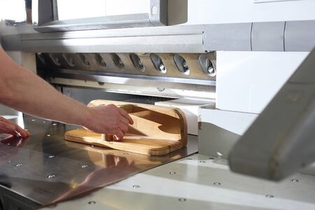 Work in the printing house. Paper trimming on a guillotine.