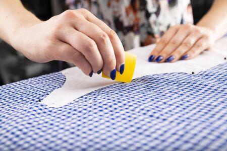 La mujer dibuja una plantilla de sastre en el material.