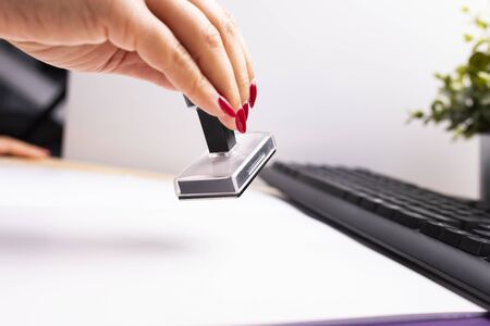 Woman with red nails at work in the office, at the desk. A female hand stamps documents by traditional, plastic, rubber stamp, on a wooden, office desk, next to the keyboard. Close-up.  Stock Photo