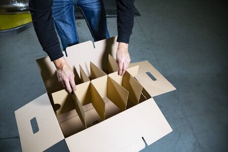 A man assembling a large, open cardboard box with compartments on the floor in a warehouse. Empty box on big gray stone floor plates. A carton box for bottles with handles. Banque d'images