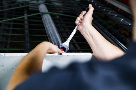 Handyman repairing a packing machine in a factory.