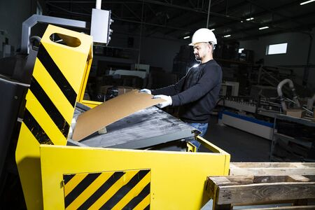 Cardboard boxes production hall. Man in hard hat putting carton into a punching machine. Paper die cutting machine.
