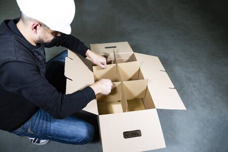 Man with a hard hat assembling a big, open, empty cardboard box with compartments on a stony floor in a warehouse.