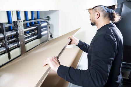 Operaio con un maglione nero e un elmetto bianco in un capannone di produzione, prendendo alcuni fogli di cartone da una pila. Produzione scatole di cartone. Archivio Fotografico