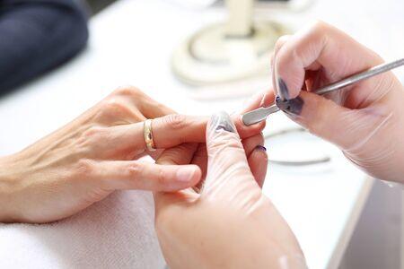 Hände, die Behandlung verschönern, Frau in einem Schönheitssalon auf einem Maniküreverfahren. Standard-Bild