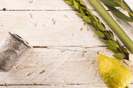 Composition of Jewish Sukkot festival symbols. The lulav - a set of four species: etrog, palm frond, myrtle and willow twigs and a kiddush cup on a light, wood background.