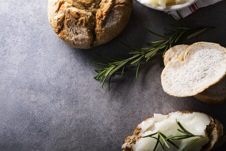 Rustic-style composition with freshly baked, crispy bread roll and sandwich with homemade lard - delicacy made of pig fat, decorated with rosemary, on a dark, stone countertop.