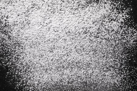 Vista dall'alto di zucchero a velo sparso su un piano di lavoro in pietra nera. Sfondo di zucchero di ricino con spazio per il testo.