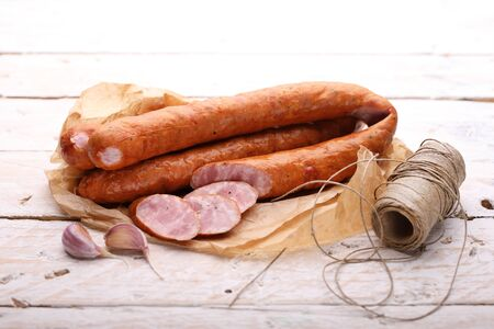 Traditional smoked sausage in rings and cut into slices on a paper and light wooden boards. Classic meat products.