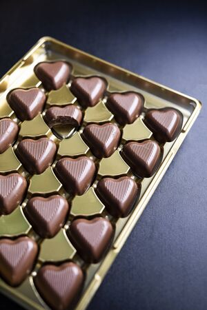 Golden box of romantic heart shaped, milk chocolates with one nibbled chocolate, on a black stony background. A box in a left corner. Valentine's Day, love, special occasion gift, sweets
