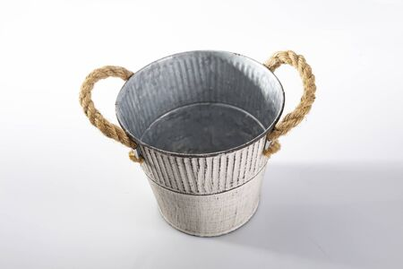 Horizontal view of an empty decorative metal flower pot cover made of steel and thick braided string, painted in a white pattern. Potted plant container, isolated on a white background.