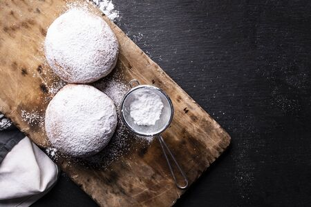 Two donuts. Sweet carnival pastries, delicacy for Fat Thursday. Top view of doughnuts covered with powdered sugar, sifter and scattered powdered sugar on the wood cutting board on a stony worktop.