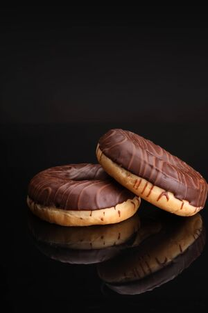 Two glazed donuts with milk chocolate topping, isolated on a black background. Sweet pastries for the Fat Thursday, carnival delicacy.