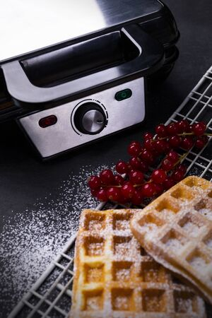 Golden waffles with powdered sugar and waffle iron on a stony worktop