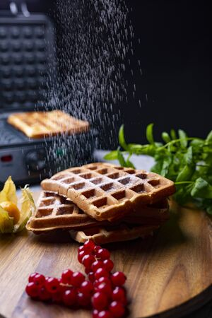 Sifting powdered sugar on classic golden Belgium waffles Stock Photo