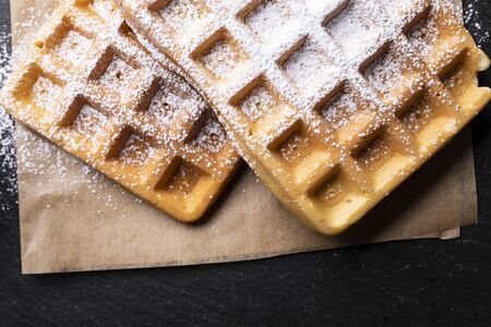 Two freshly baked waffle with powdered sugar on stony worktop Stock Photo