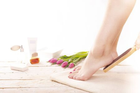 A young woman with beauty legs, using a foot file on a towel. Smoothing a heel. SPA pedicure, foot care in a cozy place decorated with pink tulips. Wellness, day SPA, beauty salon. Women's Day.