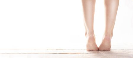 Young, female, healthy naked, bare feet standing on tiptoes on wood floor on white background. Correct foot posture. Strengthening exercises to correct flat feet. Podology. Foot care, SPA, pedicure.