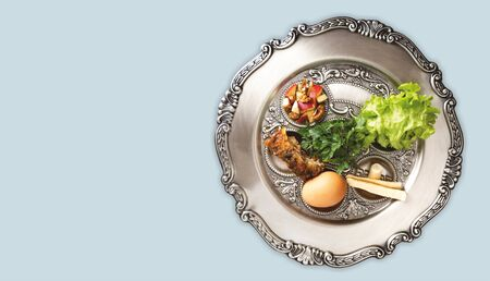 Seder plate on a dove-grey background, horizontal banner with a copyspace. Jewish seder on the occasion of Passover festival. Traditional holiday plate from Israel with Pesach symbols.