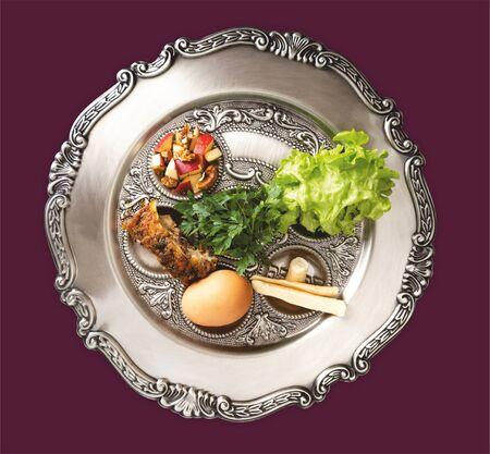 Traditional Pesach plate from Israel with five symbols: egg, bone, maror, charoset, karpas, chazeret. Seder, dinner on the occasion of Passover holiday, festival. Seder plate on a purple background.
