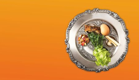 Jewish seder on the occasion of Passover festival. Seder plate isolated on an orange background, banner with copyspace. Traditional plate from Israel with Pesach symbols.