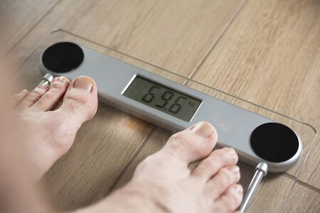 Male feet of an young fit man standing on electronic scale on a wooden-like, tile floor in a bathroom. Weight control. An underweight, slimming, weight gain, loss. Body balance.