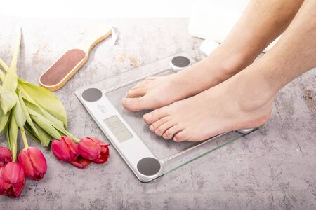 Home SPA. Healthy feet of a young fit man standing on electronic scale on a gray stony floor in a cozy bathroom, decorated with red tulips. Weight control. Body harmony, balance, relax