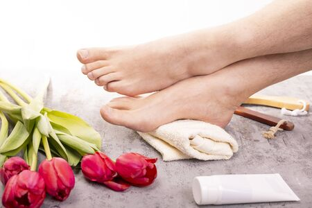 Male feet at pedicure SPA in a cozy place, on a white towel and bright gray stony floor, decorated with red tulips. Beauty, healthy male feet, heels. Home SPA, body care. Фото со стока