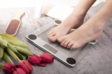 Healthy feet of a young fit man standing on electronic scale on a gray stony floor in a cozy bathroom, decorated with red tulips. Weight control. Body harmony, balance, relax