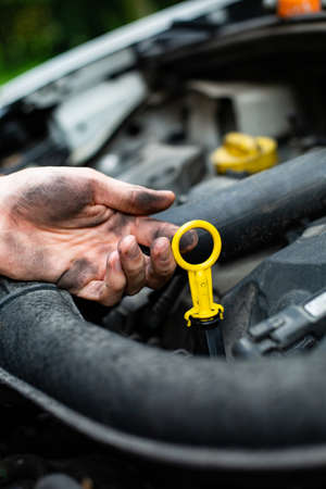 Checking car engine oil level. Vertical view of a male dirty hand holding a dipstick under the hood of the car. Vehicle check-up. Automobile service. Vehicle mechanics. Auto care and repair.