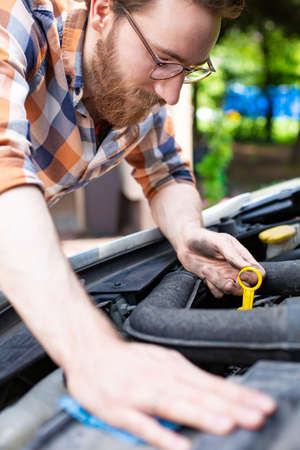 Self car care and repair. Checking car engine oil level. A bearded man looking under the hood of the car. Close-up of a handyman repairing an auto. Self automobile service. Vehicle mechanics. Stock Photo