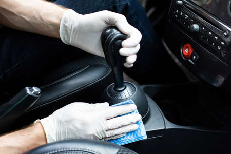 Car SPA. Man in protective gloves cleaning a car interior with high quality car detailing cosmetics. Wiping down a gearstick and a center console. Auto detailing. Automobile interior preservation. Stockfoto