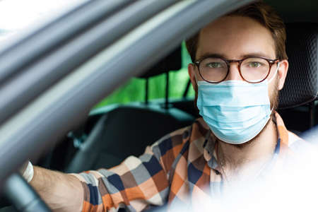 Male driver with protective gloves and a face mask, sitting in a car. Everyday prevention against infections and viruses.